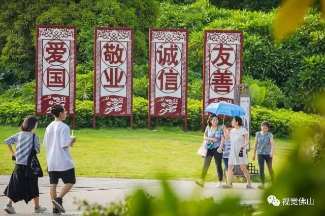"""8月22日,禅城区天地路上,几名市民在""""爱国,敬业,诚信,友善""""社会主义"""